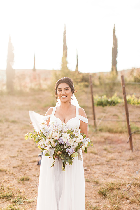 bride in a white flowing gown with off the shoulder detailing