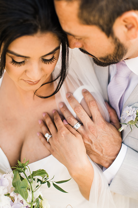 bride in a white flowing gown with off the shoulder detailing and the groom in a light grey suit with a lilac lavender long tie