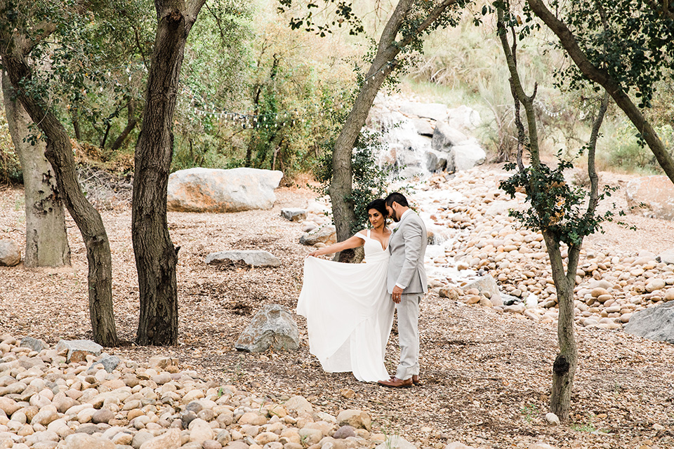 bride in a white flowing gown with off the shoulder detailing  and the groom in a light grey suit and a lavender long tie