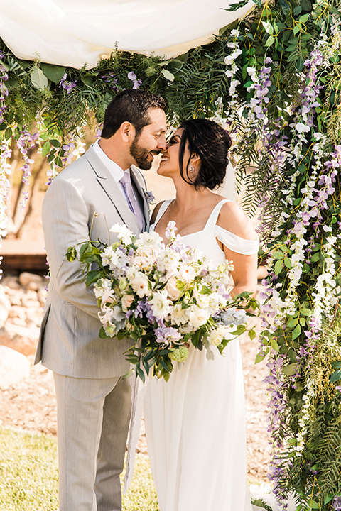 bride in a white flowing gown with off the shoulder detailing and the groom in a light grey suit with a lavender long tie