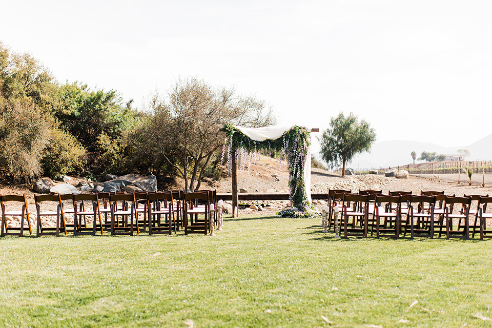 ceremony space with a wooden archway and chairs on the grass