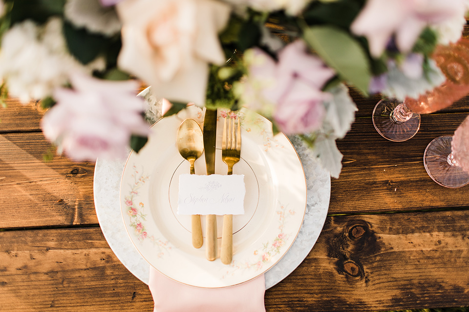 white plates with gold cutlery and lavender napkins