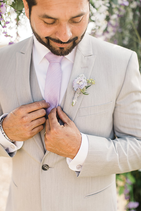 the groom in a light grey suit with a lilac lavender long tie