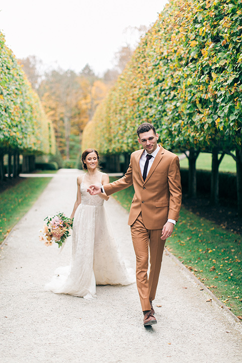 bride in a tulle ivory ballgown with a natural waist and jeweled detailing, the groom is in a caramel rust colored suit with a dark brown long tie, the walk down a path with trees and grass