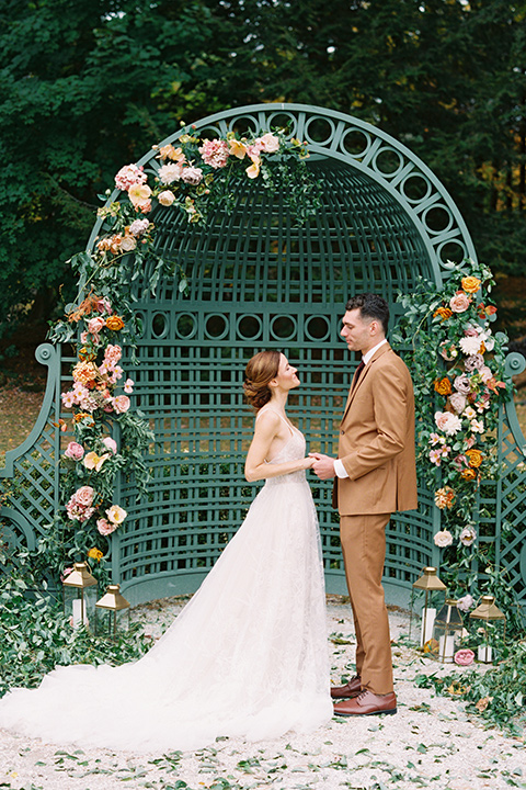 bride in a tulle ivory ballgown with a natural waist and jeweled detailing, the groom is in a caramel rust colored suit with a dark brown long tie, at the ceremony with green orange and pink floral arrangements