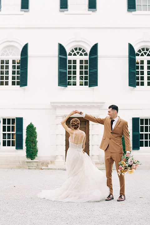 bride in a tulle ivory ballgown with a natural waist and jeweled detailing, the groom is in a caramel rust colored suit with a dark brown long tie dancing in front of the venue