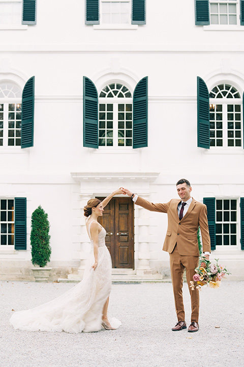 bride in a tulle ivory ballgown with a natural waist and jeweled detailing, the groom is in a caramel rust colored suit with a dark brown long tie, twirling around in front of the venue
