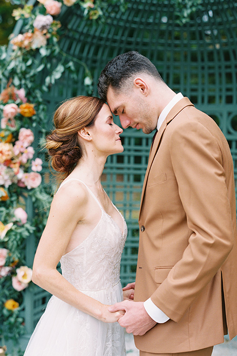 bride in a tulle ivory ballgown with a natural waist and jeweled detailing, the groom is in a caramel rust colored suit with a dark brown long tie touching their heads and smiling at the ceremony