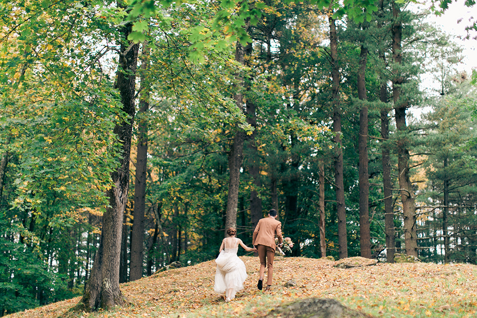bride in a tulle ivory ballgown with a natural waist and jeweled detailing, the groom is in a caramel rust colored suit with a dark brown long tie, walking up a leaf covered hill on the venue property