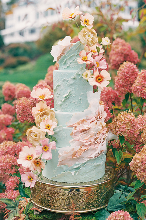 light blue cake with various pink colored flowers on it
