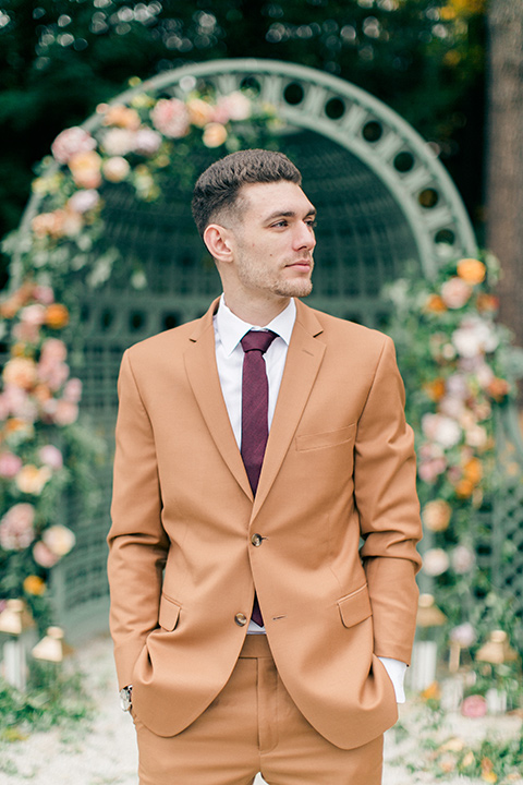 the groom is in a caramel rust colored suit with a dark brown long tie
