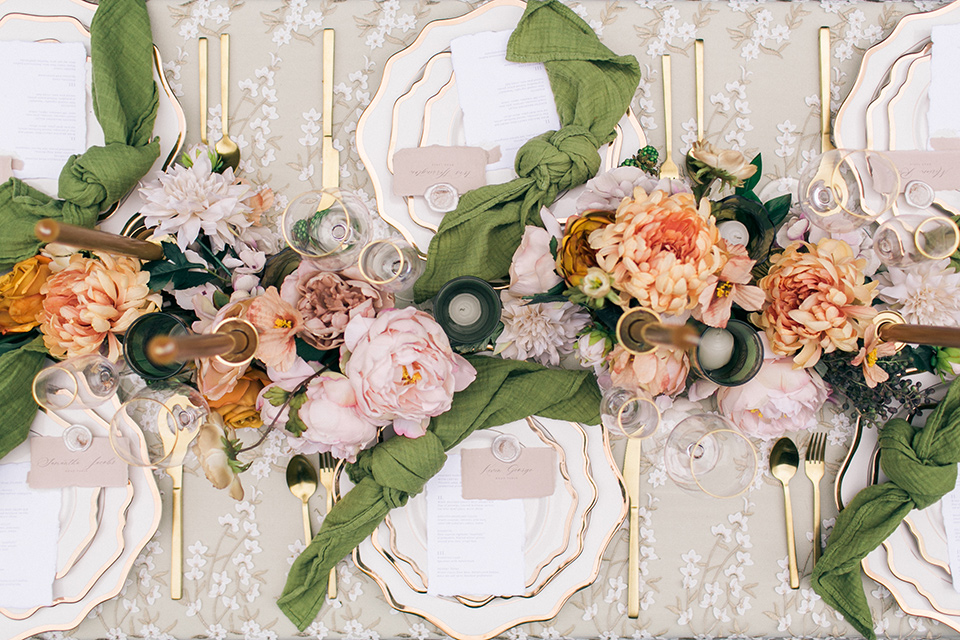 table with white linens and green napkins, tall orange candles and green and pink cascading flowers