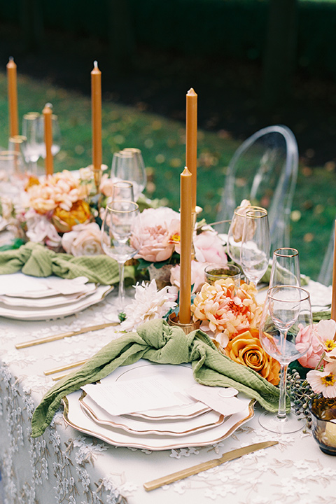 table with white linens and green napkins and orange tall candles