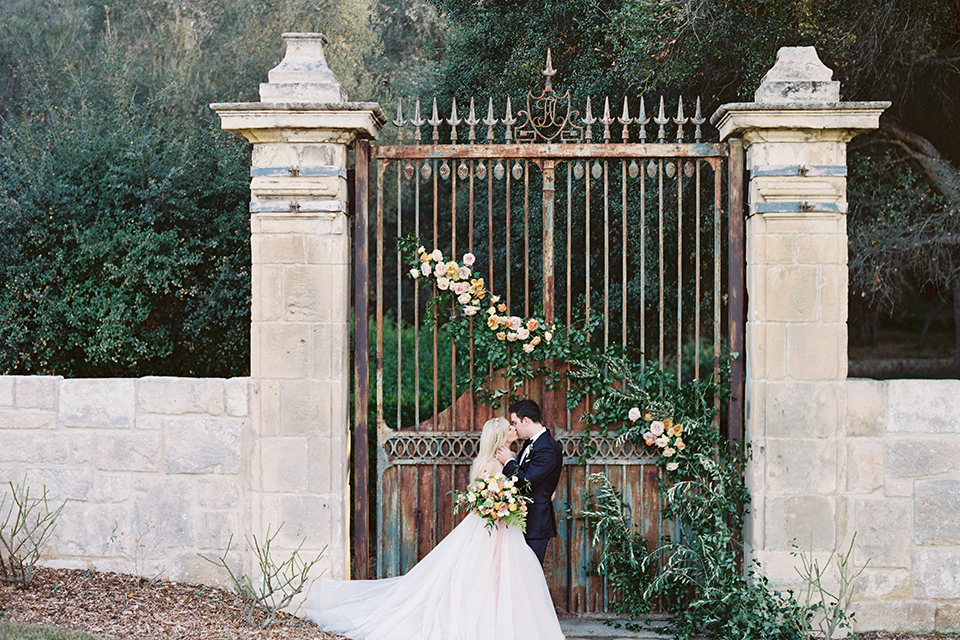 bride in a long flowing gown with long sleeves and a plunging neckline and the groom in a black tuxedo with black bow tie, kissing by iron gate