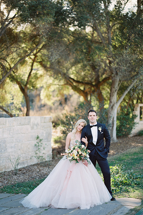 bride in a long flowing gown with long sleeves and a plunging neckline and the groom in a black tuxedo with black bow tie smiling at camera