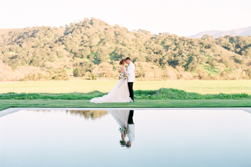 bride in a long flowing gown with long sleeves and a plunging neckline and the groom in a white tuxedo jacket with black pants and a black bow tie, walking by the water