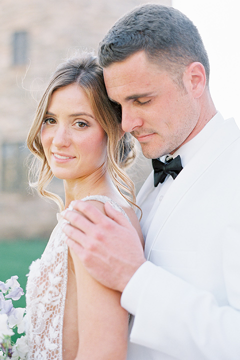 bride in a long flowing gown with long sleeves and a plunging neckline and the groom in a white tuxedo and black pants and bow tie, by brick tower