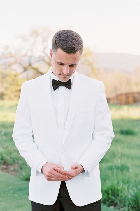 groom in a white tuxedo and black pants and bow tie, fixing his coat sleeve