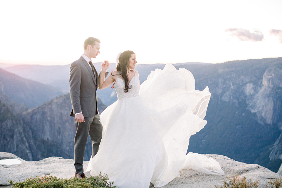 the bride with the train on the gown flowing in the wind, with her groom in a grey notch lapel suit next to her