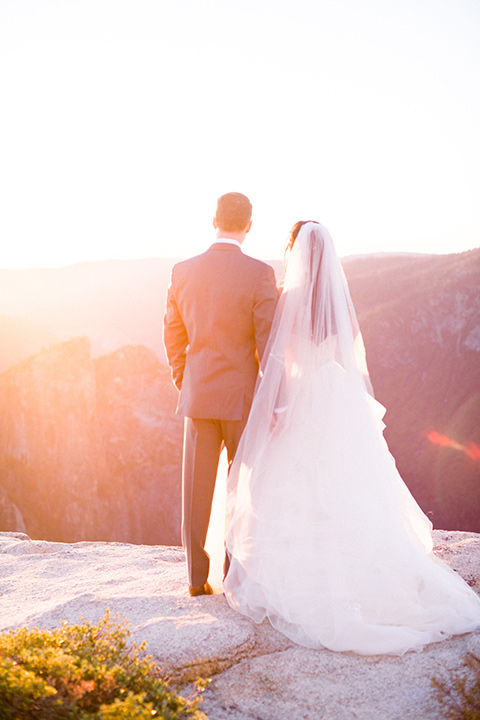bride in a white tulle gown with a grey notch lapel suit with the sunset