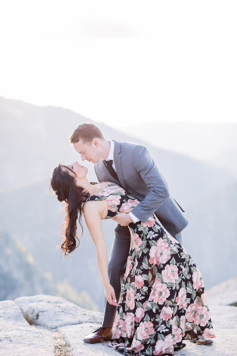 bride in a floral gown and sun hat gown with a grey notch lapel suit with the sunset