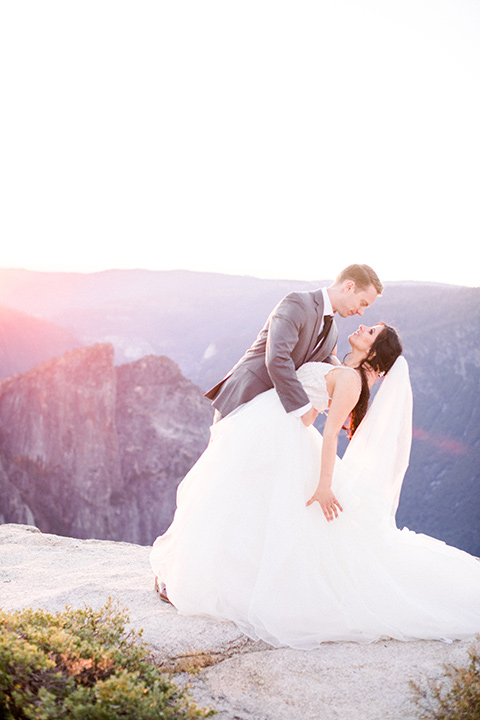 bride in tulle ballgown and long veil and the groom dipping her and kissing her with the sunset