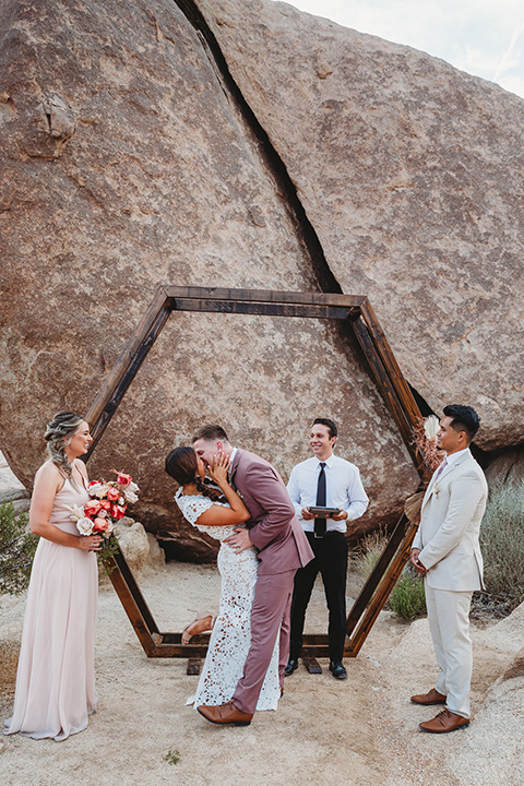 bride in a boho two-piece gown and groom in a pink suit with long tie, bridesmaid in a neutral gown and groomsman in a tan suit