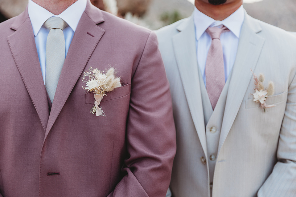 groom in a pink suit with long tie and the groomsman in a tan suit and pink tie
