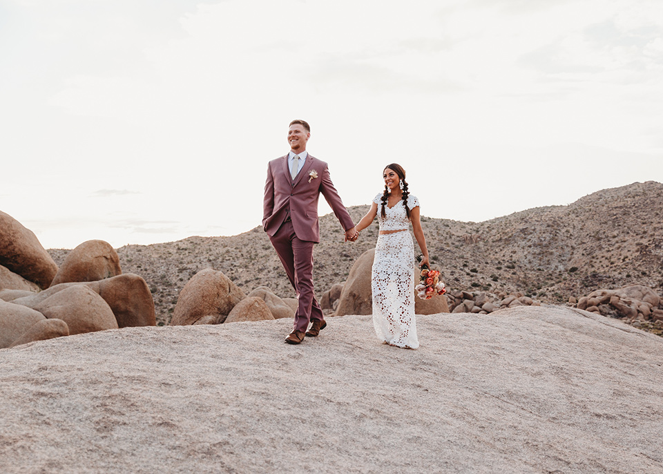 groom in a pink suit with long tie and the bride in a two piece white lace gown