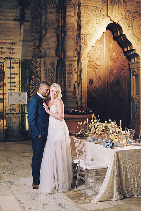 bride in a modern bohemian gown with a sheer skirt and crystal embellishments and the groom in a dark blue suit and a gold velvet bow tie