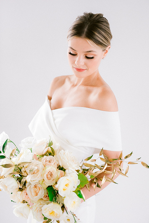 bride in a white gown with an off the shoulder detail