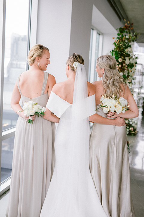 bride in a white gown with an off the shoulder detail and the bridesmaids in taupe gowns