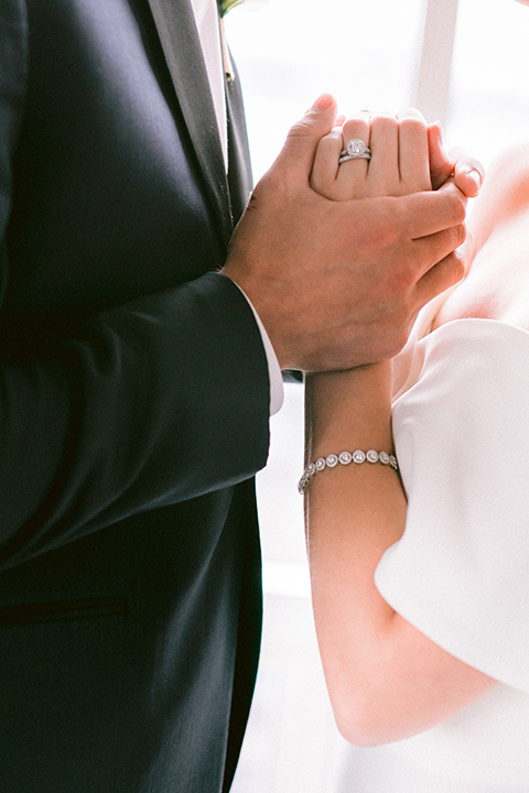 bride in a white gown with an off the shoulder detail and the groom in a blue shawl tuxedo