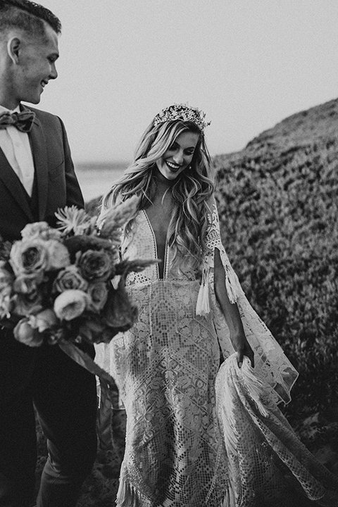 bride in a lace long sleeve gown with a plunging neckline and a boho headpiece and the groom in a rose pink suit with a gold velvet bow tie