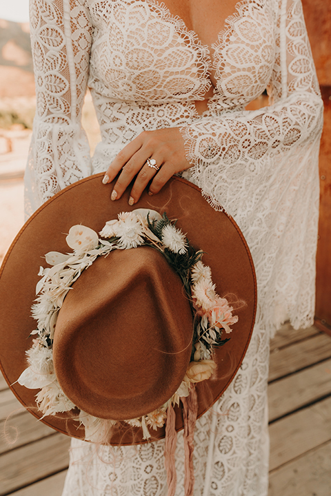 bride in a bohemian lace gown with flutter sleeves and a hat