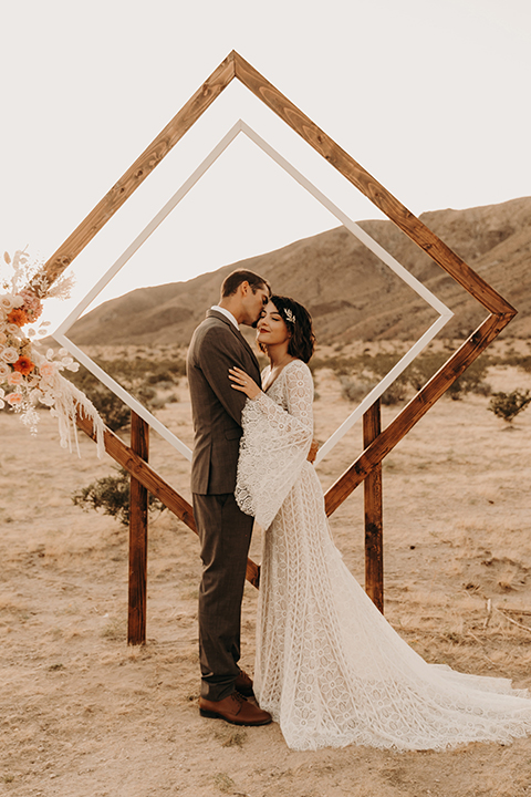 bride in a bohemian lace gown with flutter sleeves and a hat and the groom in a café brown suit with a chocolate long tie