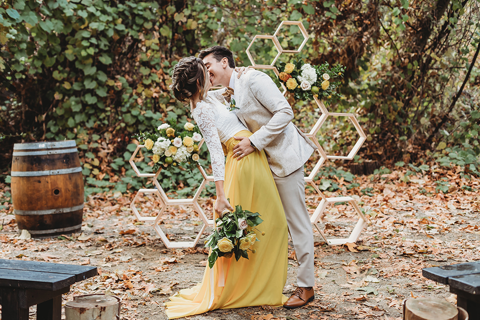groom in an ivory paisley tuxedo and gold velvet bow tie and the bride in a two-piece gown with a yellow skirt and ivory long sleeve top