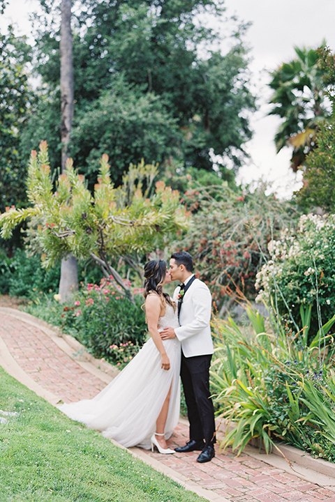 bride in a modern gown with a strapless neckline and the groom in a white tuxedo and bow tie