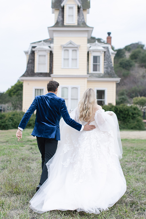 groom in a blue velvet tuxedo and a black bow tie and the bride in a white flowing gown with bell sleeves