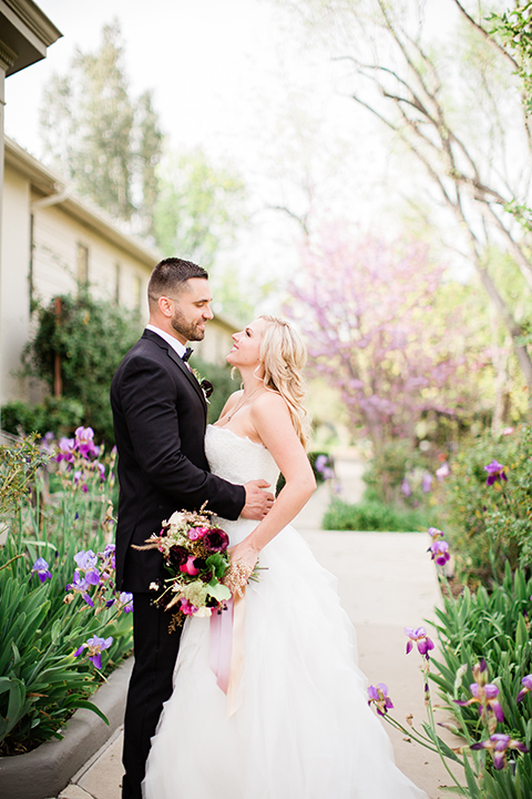 bride in a strapless white ball gown and the groom in a black tuxedo with black bowtie