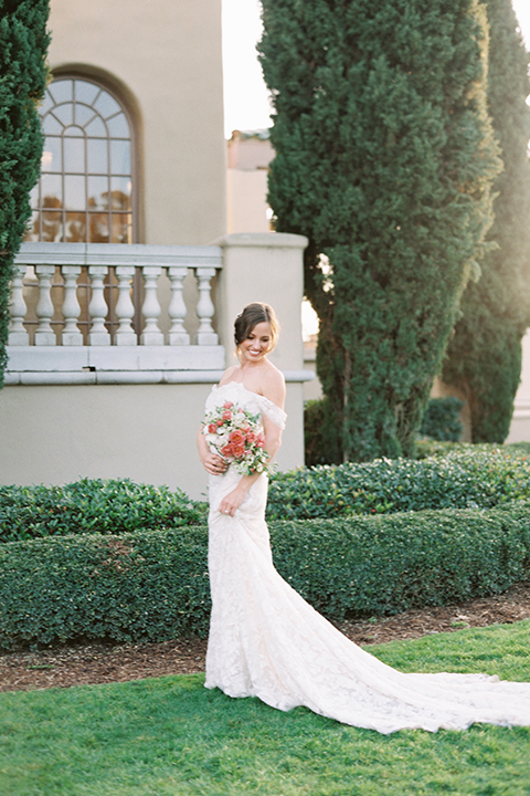bride in a formfitting white lace gown with an off the shoulder detail