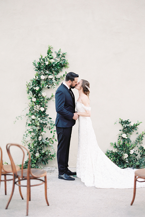 bride in a formfitting white lace gown with an off the shoulder detail  and the groom in a navy shawl lapel tuxedo