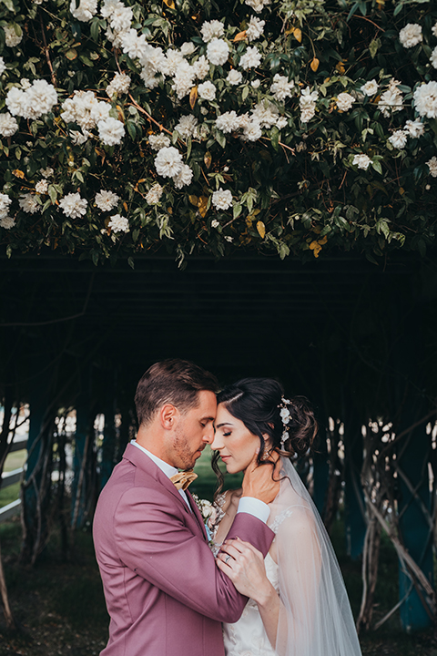 bride in a flowing lace gown and the groom in a rose pink suit