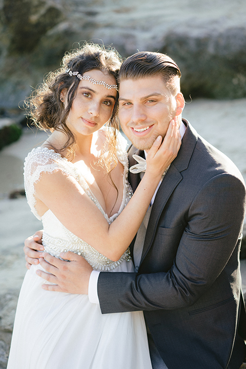 bride in  flowing gown with embellishments and the groom in a dark grey coat with light grey pants