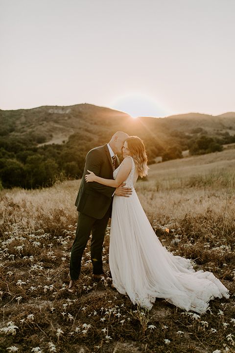bride in a long white gown with a long train and boho hat