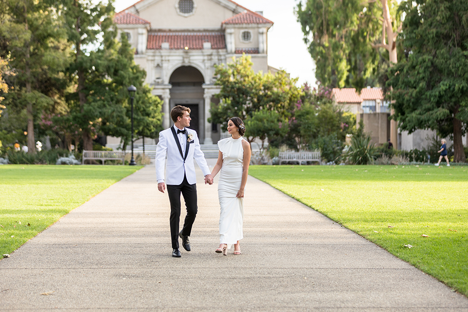 bride in a white modern gown with a high neck and cap sleeves, the groom in a white shawl lapel tuxedo and a black bow tie