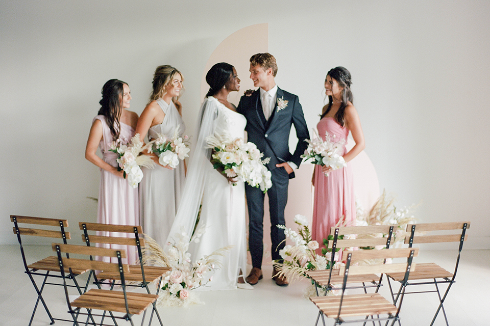 bride in a modern white form fitting gown with a cape, the groom in a slate blue suit and the bridesmaids in different shades of pastel