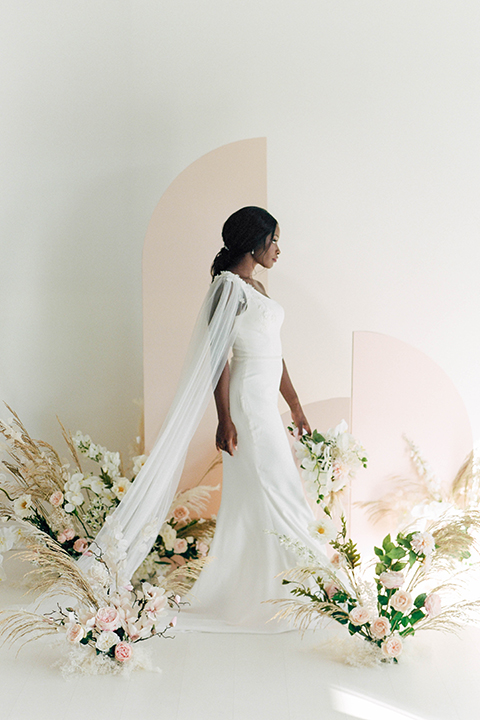 bride walking in a white long gown with a cape and her hair in a ponytail