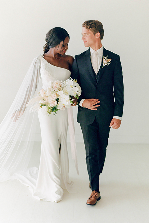 bride in a white formfitting modern gown and cape and the groom in a slate blue suit with a silver long tie