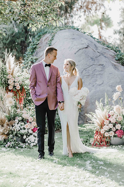 the bride and groom at the ceremony – the bride in a white lace gown and the groom in a rose pink coat and black pants